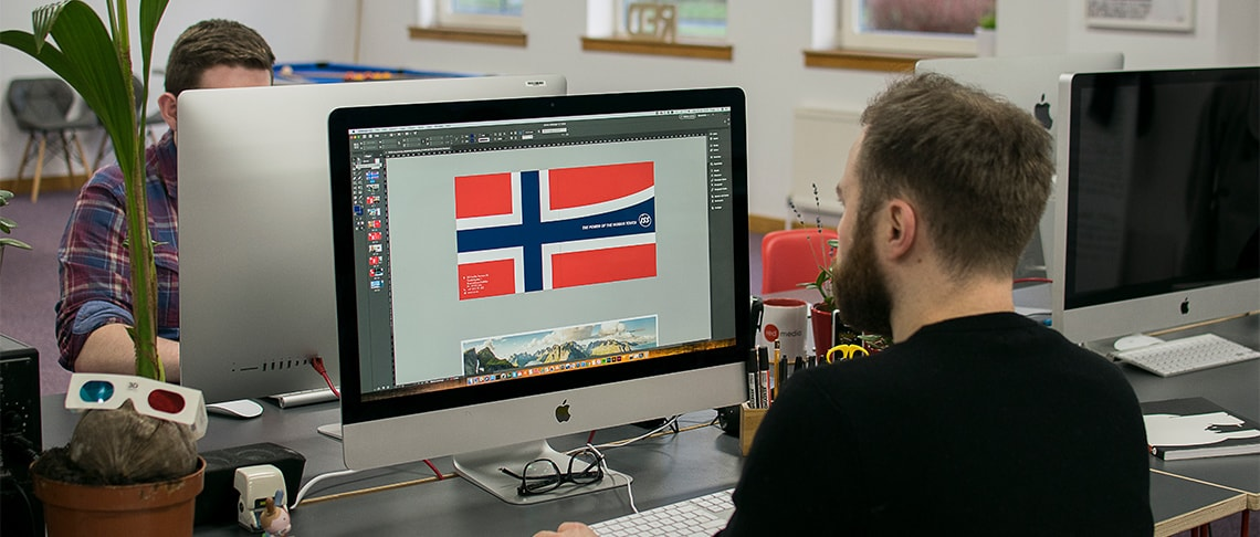 Red Media graphic designer working at a computer designing a corporate brochure for ISS Norway