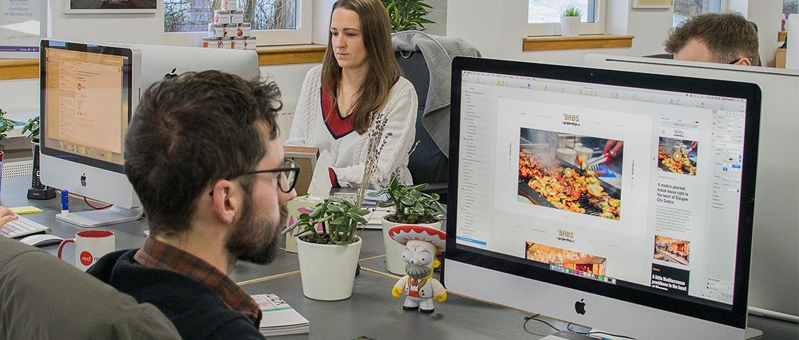 Red Media designer working at a computer designing a website for 'Bab's restaurant.