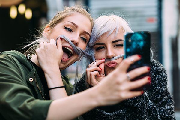Red Media: Marketing Millenials via Snapchat blog post cover, with a red and purple gradient background and Red Media logo, and a faded image of two girls taking a selfie